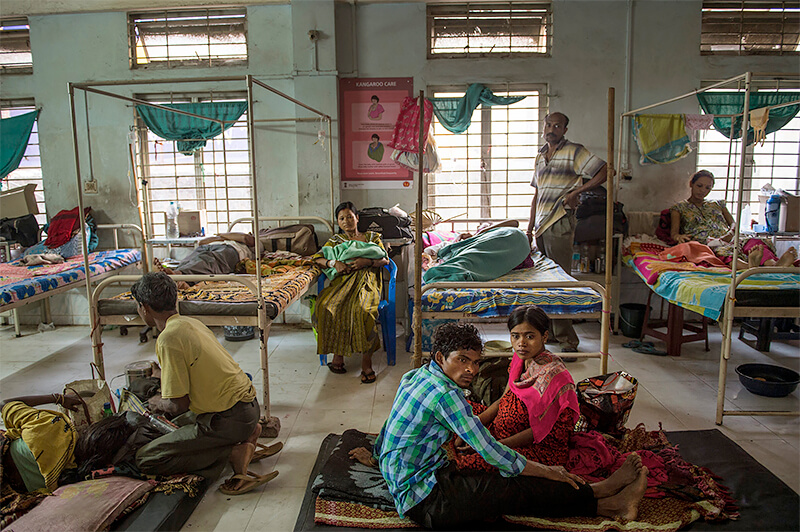 Lynsey Addario><p class=f12 l16 pt5 right>Indian families rest in a ward reserved for women recovering from cesarean sections, at Tezpur Civil Hospital. Assam has the highest rate of maternal mortality in India. Many public medical facilities are overcrowded and unhygienic, suffer from a chronic shortage of doctors, and often have patients sprawled on floors and in hallways. Tezpur, Assam, India. April, 2015.<br