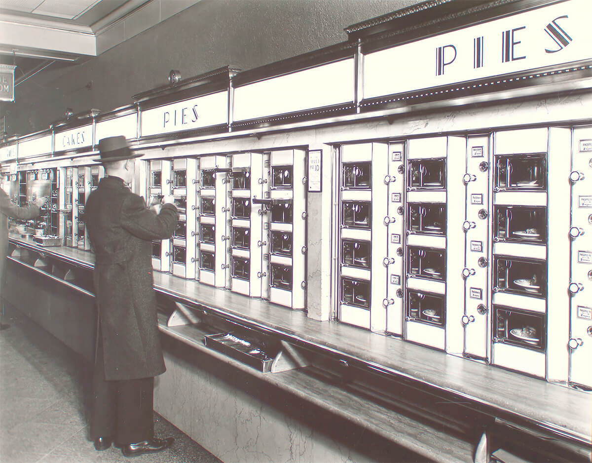 Man takes pie out of Automat, stone counters and walls below metal and glass display 1936 ©New York Public Library<p>© Berenice Abbott</p>
