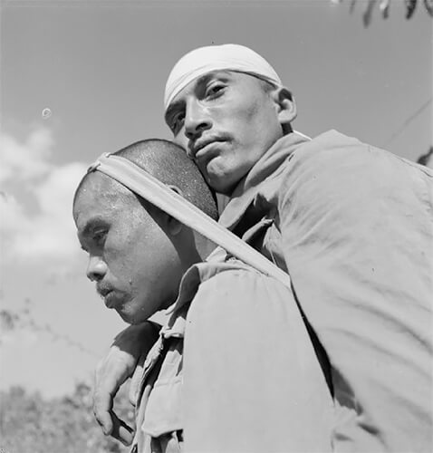 Cecil Beaton - India 1944: A Gurkha soldier transporting a wounded man on his back through the jungle. © IWM Non Commercial Licence