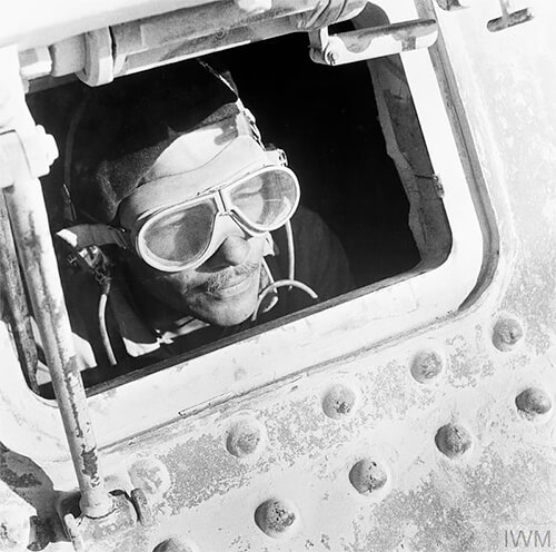 Cecil Beaton - Cecil Beaton portrait of a British tank driver peering out of his Grant tank in North Africa, 1942. © IWM Non Commercial Licence