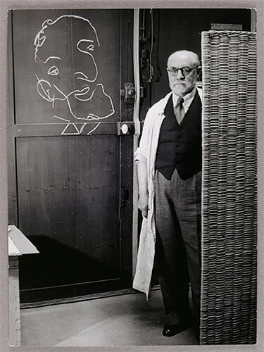 George Brassaï - Henri Matisse standing against a screen and drawing with chalk, 1939