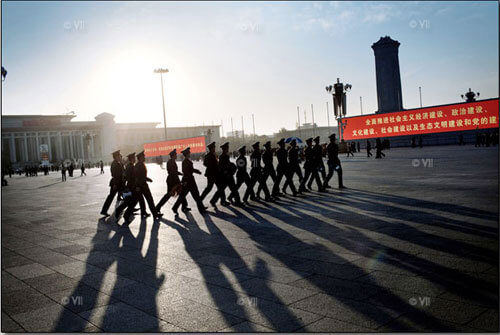 Chinese military walk in formation across Tiananmen Square just seconds after they detained scores of people, Beijing.<p>© Marcus Bleasdale</p>