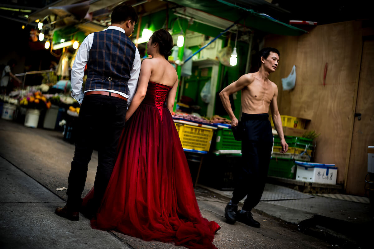 Hong Kong, China - Woman in a red velvet evening dress standing in a street with her boyfriend on May 01, 2018<p>Courtesy Redux Pictures / © Jean-Michel Clajot</p>