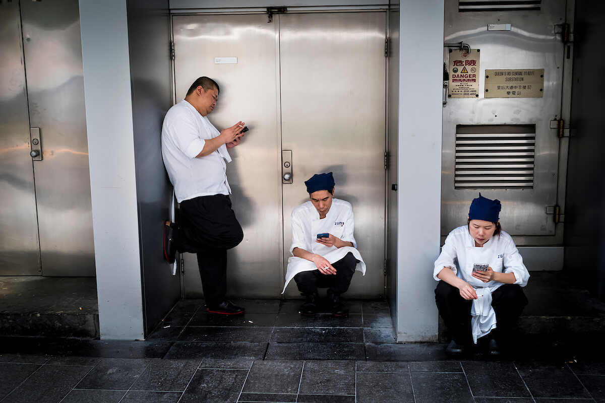 Men and woman smokes and checks their mobile phone on a street in Hong Kong during a work break on April 30, 2018<p>Courtesy Redux Pictures / © Jean-Michel Clajot</p>