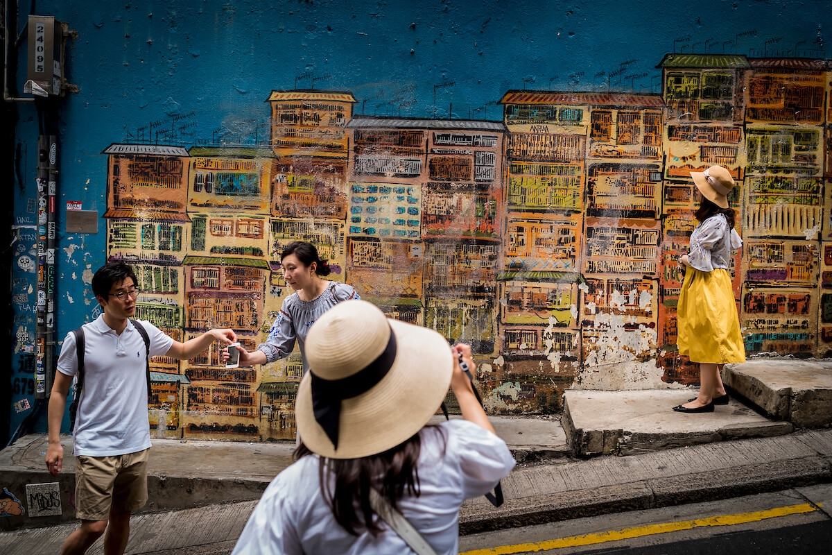 Tourists pose for photographs in front of street art along Graham Street in Hong Kong's SoHo district on April 30, 2018<p>Courtesy Redux Pictures / © Jean-Michel Clajot</p>