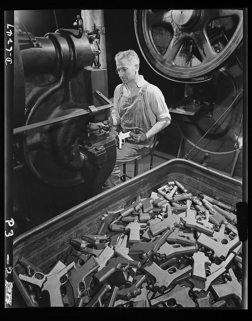 John Ignacek pierces trigger hole guards on .45-caliber automatic pistols in the plant of a large manufacturer of firearms. 1942<p>© Andreas Feininger</p>