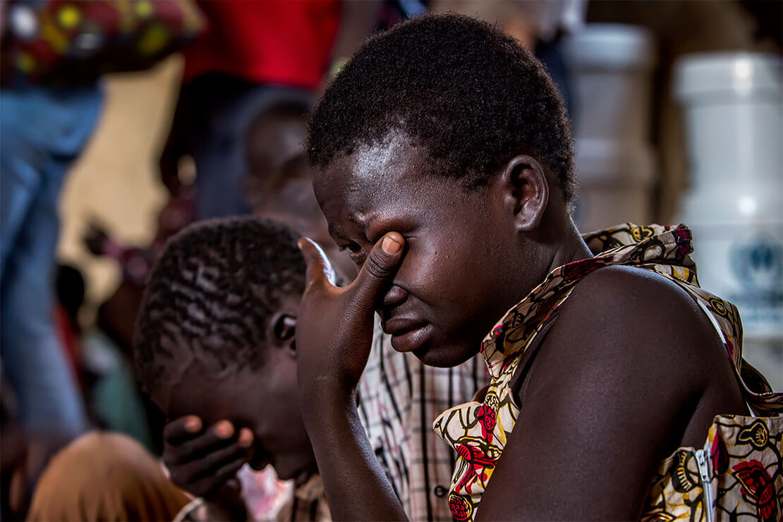 Elizabeth Aguek Lino, 16, cries as she recounts to Refugees Chief Filippo Grandi how her father and brother were shot and killed in South Sudan. <p>© Georgina Goodwin</p>