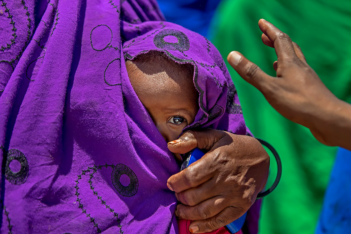 Peering through the folds in her mother's dress was this beautiful girl in a makeshift camp in central Somaliland<p>© Georgina Goodwin</p>