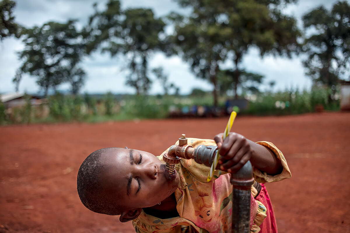 Burundi refugee students drink from the tap at Jugudi Primary School at Nyarugusu Refugee Camp in Kasulu District, western Tanzania, 2019<p>© Georgina Goodwin</p>