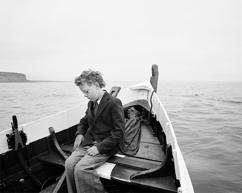 Simon Coultas being taken to sea for the first time since his father drowned, Skinningrove 1984<p>© Chris Killip</p>