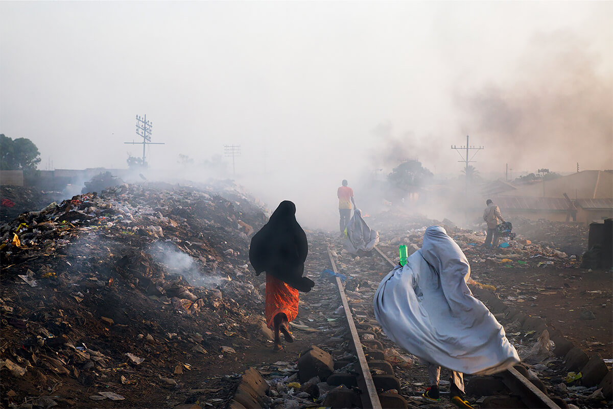 Locals go about their routines, stepping over garbage heaps that burn along the railroad tracks in Kaduna, Nigeria on April 3, 2013.<p>Courtesy VII Photo Agency / © Ed Kashi</p>