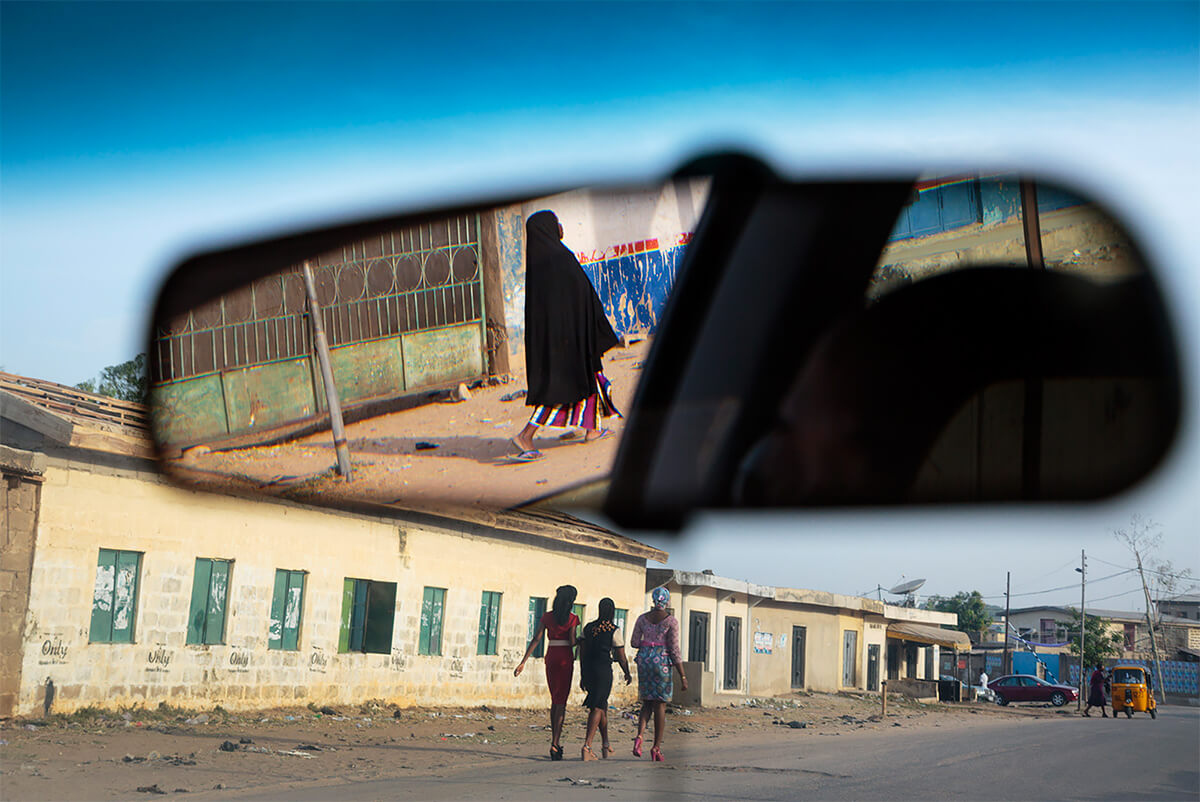 A Muslim woman is reflected in a car mirror while Christian women are seen walking down the street in Kano, Nigeria, on March 31, 2013.<p>Courtesy VII Photo Agency / © Ed Kashi</p>