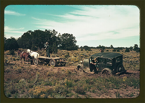 Russell Lee - A horse-and-cart team pulling a car out of the mud on a road near Pie Town, New Mexico, in late 1940.