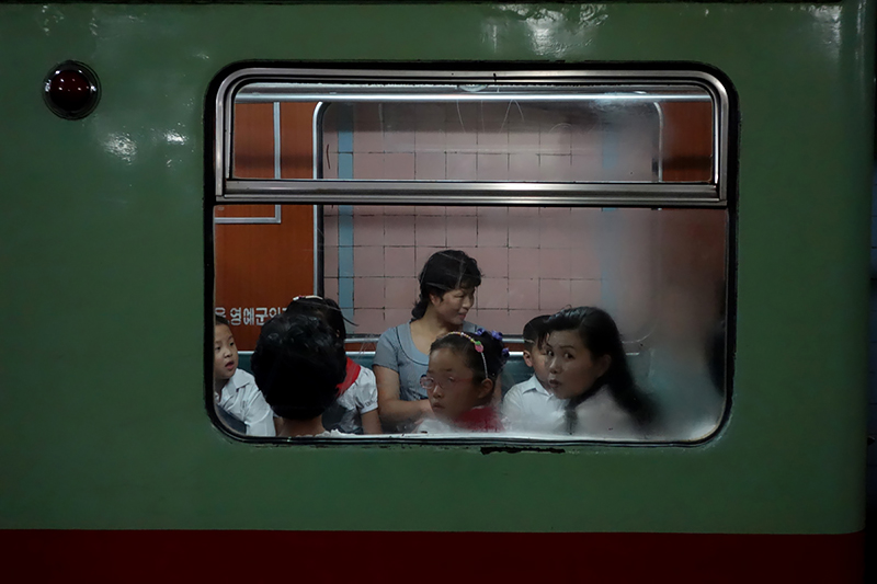 Fabian Muir - Commuters stare at Muir through the train window in the Pyongyang metro on August 20, 2014.