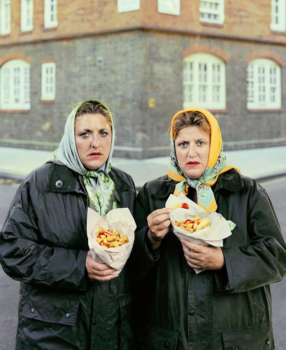 Sisters in scarfs eating pimlico chips<p>© David Stewart</p>